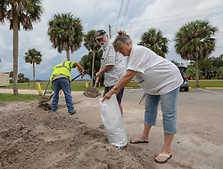 October 10, 2018 - Weeki Wachee, Florida, U.S. - DOUG HODGINS, left, along with his wife LINDA, of Panama City load sand in bags at Linda Pedersen Preserve in Weeki Wachee. The couple live on a boat in Panama City and were forced to leave as Hurricane Michael barreled toward the coast. The Hodgins are staying at Doug's brother's home but fear a high tide may later this afternoon may flood the home. (Credit Image: © Chris Urso/Tampa Bay Times via ZUMA Wire)