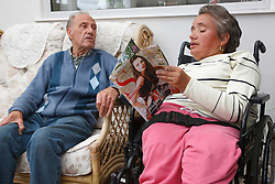 Wheelchair user with Spina Bifida reading a magazine and talking to her father.