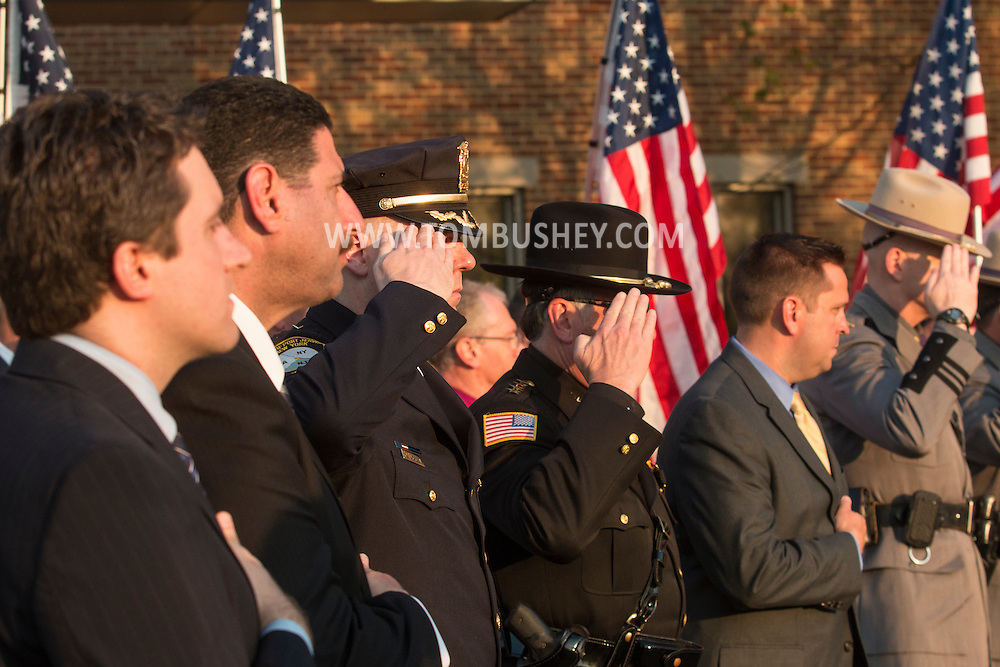 Goshen, New York - Police officers and dignitaries salute during the Orange County Law Enforcement Officer Memorial Service on May 8, 2015, at the entrance of the Orange County Courthouse. The memorial service honors the memory of the members of the Orange County law enforcement community that died in the line of duty. The service also pays tribute the families and loved ones left behind for their courage, dignity and perseverance.