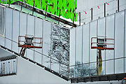 Construction lifts are reflected in the glass of the under-construction architecture building.