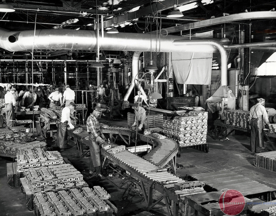 Studebaker Foundry workers perform finishing work on freshly-cast cylinder heads.