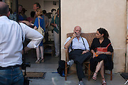 """Ferdinando Scianna, Italian photographer member of Magnum agency, sitting with a woman outisde the Anne Clergue Galerie in Arles, July 5, 2016. It's the opening day of his exhibition """"La Sicile et Marpessa"""", at the Anne Clergue Galerie. © Carlo Cerchioli"""