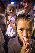 "04 FEBRUARY 2013 - PHNOM PENH, CAMBODIA:  A Cambodian boy prays at the cremation of their former King Norodom Sihanouk during the King-Father's cremation service in Phnom Penh. Norodom Sihanouk (31 October 1922 - 15 October 2012) was the King of Cambodia from 1941 to 1955 and again from 1993 to 2004. He was the effective ruler of Cambodia from 1953 to 1970. After his second abdication in 2004, he was given the honorific of ""The King-Father of Cambodia."" Sihanouk died in Beijing, China, where he was receiving medical care, on Oct. 15, 2012.   PHOTO BY JACK KURTZ"