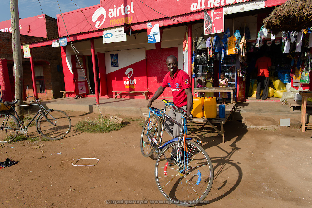 Ali Kinene of Plan Uganda pretends to steal a bicycle near Tororo in eastern Uganda on 2 August 2014.