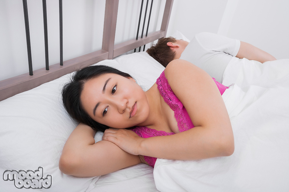 Displeased woman with man sleeping in bed