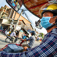 Jan 3, 2013 - A Tuk Tuk driver uses a surgical mask, which does little to filter out harmful particles and gases in air pollution, navigates traffic through the Cambodian capital city of Phnom Penh.<br /> <br /> Story Summary: It is said that the battle over global warming is to be won or lost in Asia. With growing populations and new economic boom in the global markets across Asia countries like India, Nepal and Cambodia have to grapple with the success and the environmental disaster that comes with ramped up production in unchecked or unregulated industries to compete in todays marketplace. The catastrophic air pollution makes for new problems to be dealt with such as a future health crisis, quality of life issues and the tarnished image of reduced visibility to world heritage sites for tourism.