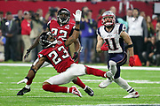 New England Patriots wide receiver Julian Edelman (11) looks up for the ball while defended by Atlanta Falcons cornerback Robert Alford (23) and Atlanta Falcons rookie strong safety Keanu Neal (22) as he looks to make a circus catch on a pass reception good for a gain of 23 yards and a first down at the Falcons 41 yard line on a key fourth quarter drive with two minutes left in regulation play during the Super Bowl LI football game against the Atlanta Falcons on Sunday, Feb. 5, 2017 in Houston. The Patriots won the game 34-28 in overtime. (©Paul Anthony Spinelli)