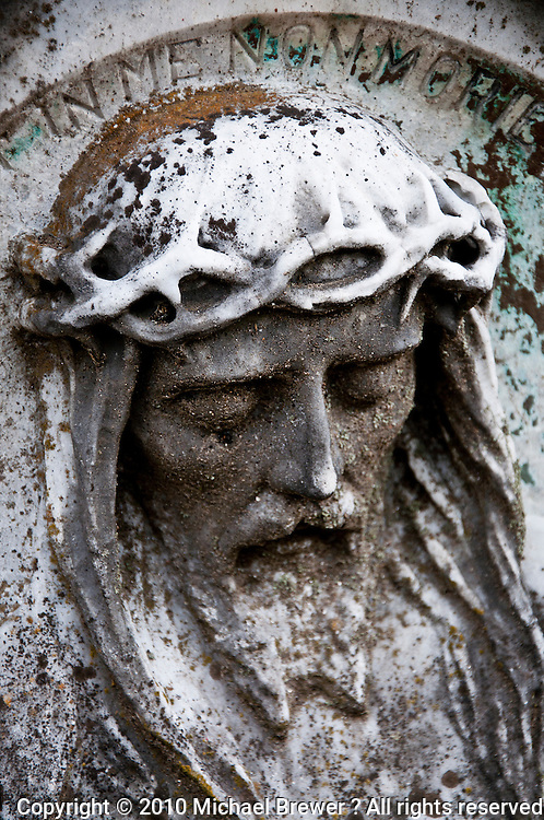 Ticino, Southern Switzerland. Old, weathered, marble tombstone with a relief of a suffering Jesus carved into it.