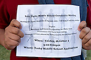 A studentfrom Sam Tasby Middle School in Dallas, Texas holds up a flyer given to all students inviting families to a community meeting based around the Ebola outbreak on October 2, 2014. Officials confirmed that a student at Sam Tasby Middle School had come in contact with the first confirmed Ebola virus patient in the United States. (Cooper Neill for The New York Times)
