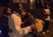 Pastor in white shirt embraces a crying mother, Syreeta Myers, who has come to the vigil of her son, instead a fierce shootout broke out.<br /> <br /> At a vigil to commemorate the death of 18 year old VonDerrit Myers Jr. at the hands of an armed security guard, an dispute breaks out between two groups at the street intersection.<br /> At least four shooters are involved in a violent 2 minute shoot out which saw at least 58 bullets fired. Participants dive for cover and flee.<br /> Once it is over, one man lies injured, others are sped away in vehicles or run off. Blood and shell casings litter the street, and as the police secure the crime scene, the pastor calls the people to gather around and continue the vigil to honor the dead teenager. Another day of urban violence in the USA.