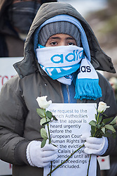 © London News Pictures. Calais, France. 07/03/16. A young boy stands with white flowers and a sign calling for the demolition to be halted until the European Court of Human Rights is allowed to adjudicate on its legality. French authorities are evicting and demolishing the southern half of the Calais 'Jungle' camp, which charities estimate to contain 3,500 people. . Photo credit: Rob Pinney/LNP