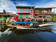 27 SEPTEMBER 2016 - BANGKOK, THAILAND: A tourist boat goes past house near the floating market in Damnoen Saduak, Thailand. The market is famous because vendors cruise the canals around the market selling produce and tourist curios. It is one of the best known tourist attractions in Samut Songkhram province.     PHOTO BY JACK KURTZ