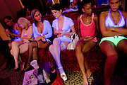 "Sex workers, from left, Nina Nicole, Rhiannon, Erin Daye, Mila Moore, Kitten, and Skye High sit in the parlor of the Moonlite Bunny Ranch brothel in Mound House, NV on Friday, July 28, 2006...The Moonlite Bunny Ranch brothel in Mound House, Nevada - just a few miles from the state capital in Carson City - first opened in 1955. The Ranch is a legal, licensed brothel owned by Dennis Hof. It's featured in the HBO series ""Cathouse."""