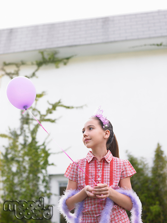 Girl (10-12) in feather boa holding balloon outside house