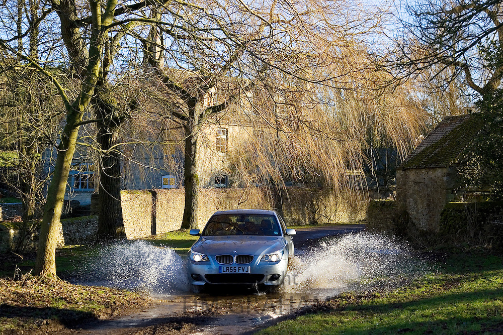 BMW 5 Series car drives through country lane ford, Swinbrook, Oxfordshire, United Kingdom