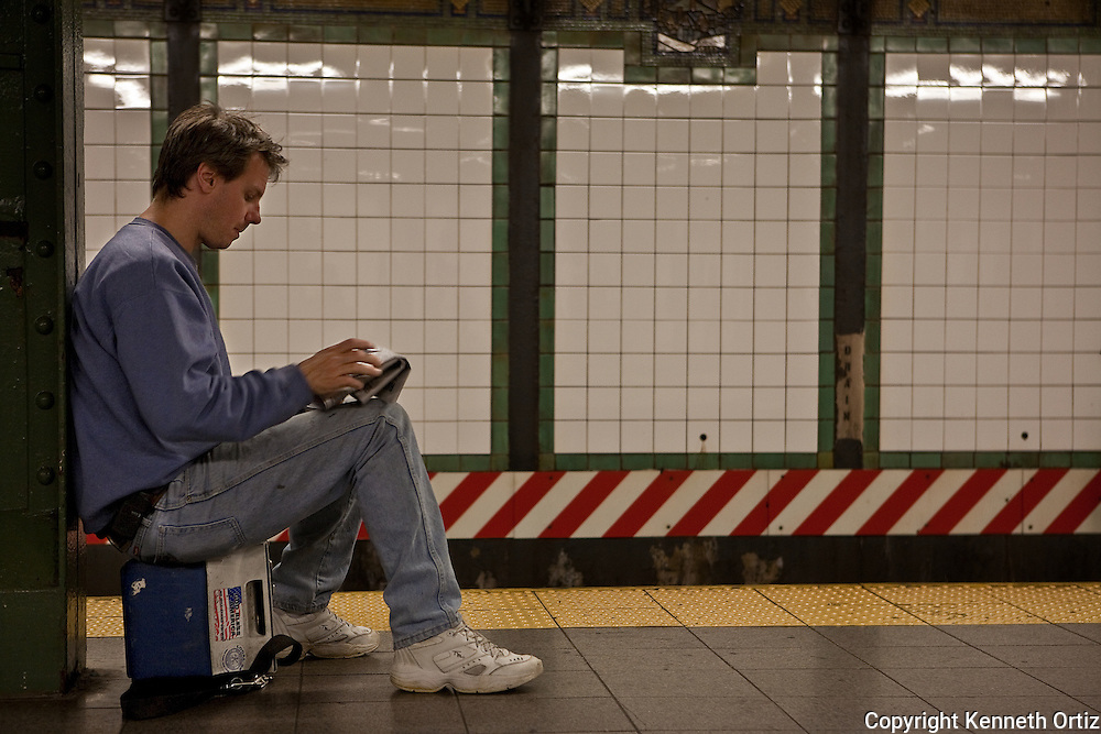 A construction worker sitting on his lunch box waiting for  the train to arrive while reading the daily newspaper.
