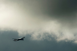 © Licensed to London News Pictures. 03/03/2014. LONDON, UK A british Airways plane flies under storm clouds in West London this afternoon 3rd March 2014. Photo credit : Stephen Simpson/LNP