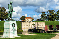 A war memorial statue in the area of Kastellet in Copenhagen showing an old fort and some greenery, a bridge over a river.