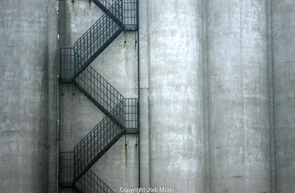 A fire escape on the side of a large silo.