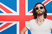Portrait of young man in white t-shirt wearing sunglasses against British flag