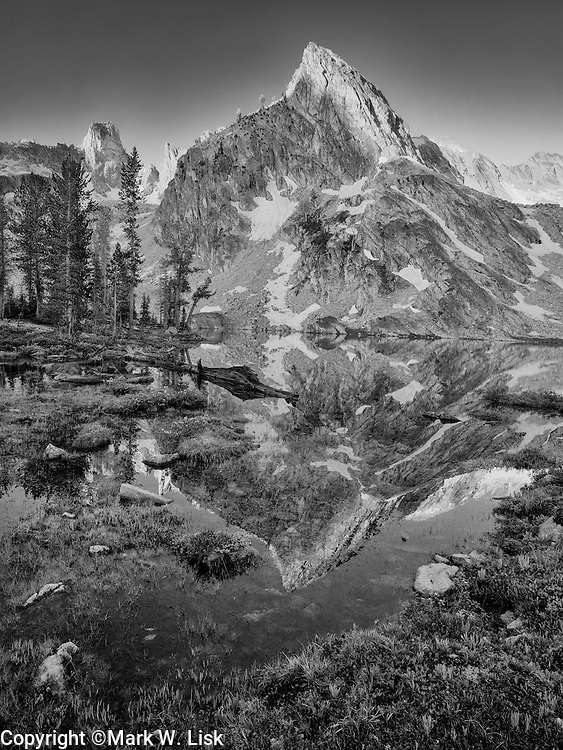 Massive walls of exposed granite towers above the tranquill water of Twin Lakes in the Sawtooth Wilderness.