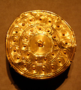 Gold Disk from a Reel.  Bronze Age, found in Enniscorthy, Ireland.  Made about 800 B.C.  Ireland experienced a period of resurgence in the production of gold work during the late Bronze Age.  Numerous objects noteworthy for their gold content, innovative