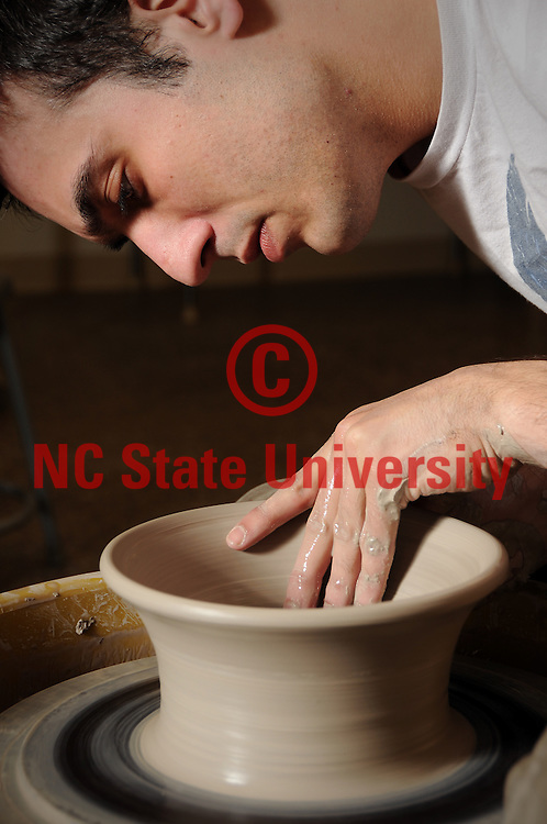 Student throws a pot at the Craft Center in Thompson Hall.