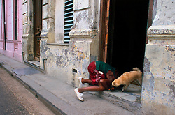 A boy plays with his dog in the doorway of his home in Havana, Cuba. (Photo © Jock Fistick)