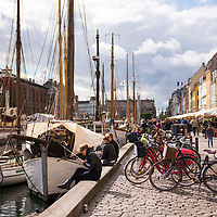 Nyhavn, or the New Harbor, is lined with colorful 17th and early 18th century buildings and is a popular tourist attraction in downtown Copenhagen, Denmark.