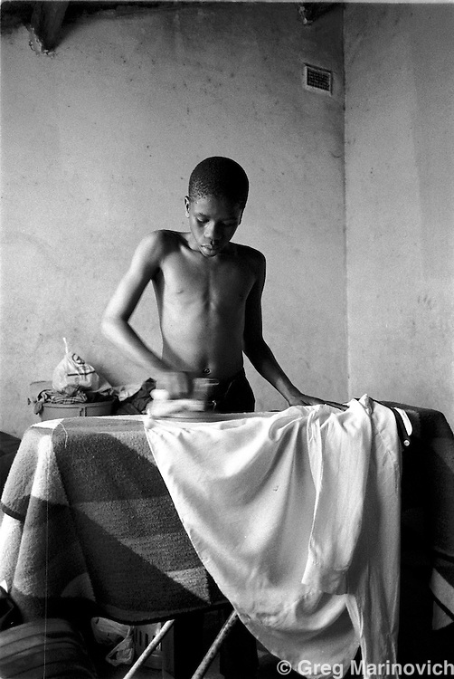 IPMG0564 South Africa, Ngwelezana 2000: .Sixteen year old Sifiso Hlongwe irons his shirt for the funeral of his mother, AIDS activist Deli Hlongwa in Ngwelezana in the KwaZulu Natal province of South Africa, March 25, 2000 on the day of her funeral.  Deli was a person living with full-blown AIDS who took part in the local `Funeral Campaign' where people with HIV and Aids tell others in he community of their disease and invite them to come look at them in their open casket when they die, to disprove the widely-held notion that HIV does not kill.  South Africa has a rapidly growing HIV crisis, with some 25% of ante-natal women testing positive...Photograph by Greg Marinovich/South Photographs