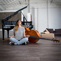 Young Double bass player sitting on the ground in front of a grand piano.