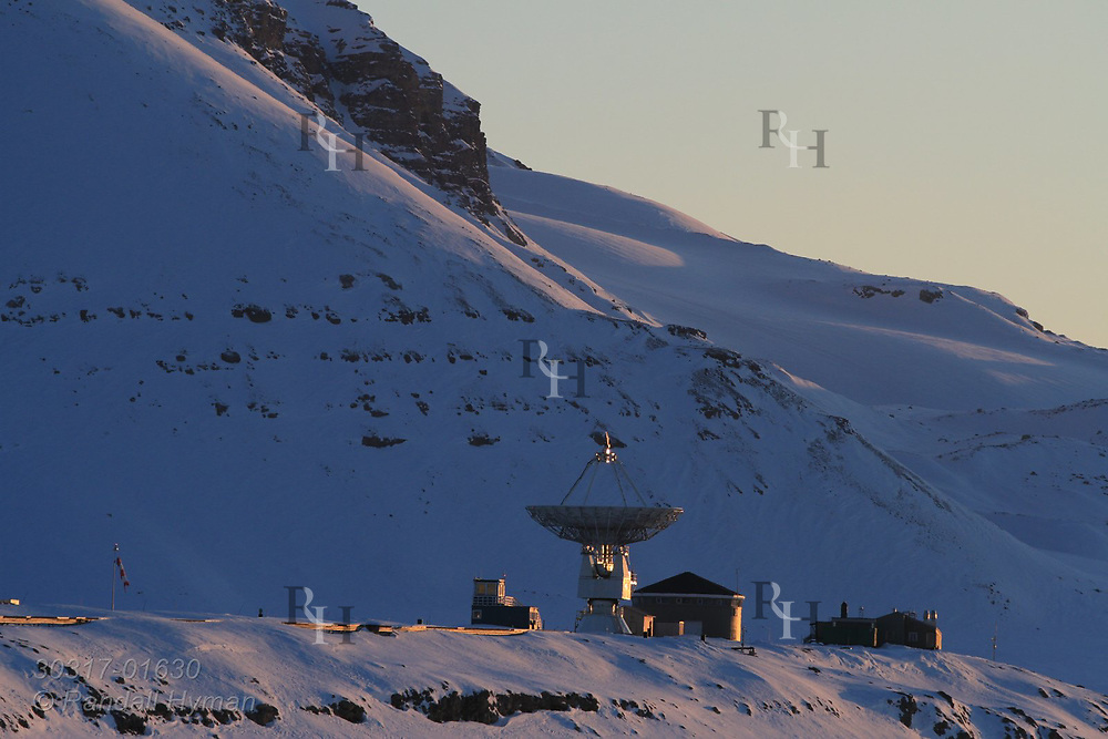 Evening sun of April lights the VLBI radio telescope at Hamarabben Airport above the international science village of Ny-Alesund on Spitsbergen island in Kongsfjorden; Svalbard, Norway.
