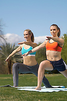 Two young women performing yoga exercises in park
