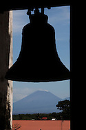 A view from the tower of La Asuncion Cathedral in Leon, Nicaragua. showing the bell with San Cristobal volcano in the background.  Photograph by Dennis Brack