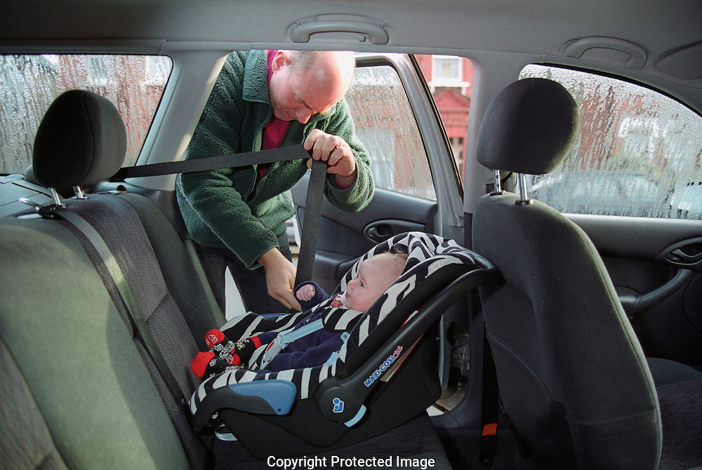 Father putting baby into baby seat in car before journey.