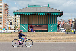 © Licensed to London News Pictures. 18/04/2014. Brighton, UK. A young girl cycles along the seafront.  People enjoy the  bank holiday sunshine at Brighton today 18th April 2014. Photo credit : Stephen Simpson/LNP