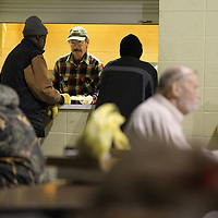 Scott Womack serves dinner before the gym at the Salvation Army before the space is transformed into a shelter for those needing a warm place to sleep.