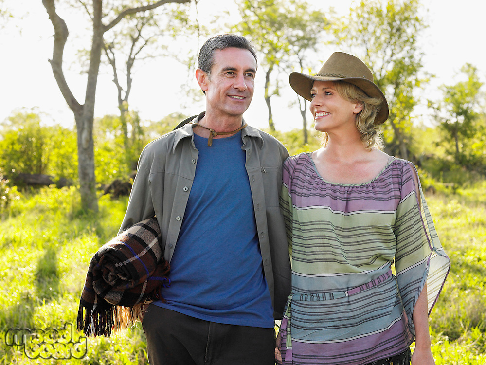 Adult couple outdoors man carrying blanket woman wearing hat smiling