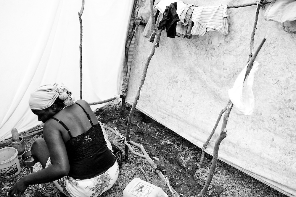 A woman cooks dinner in a tent city comprised of people displaced by the recent earthquake in Port-au-Prince, Haiti.