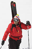 Male skier hiking up mountain slope