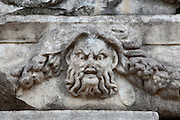 Mask and garland frieze from the Portico of Tiberius on the Southern portico of the Agora, 1st century AD, Aphrodisias, Aydin, Turkey. The Sculpture School at Aphrodisias was an important producer of carved marble sarcophagi and friezes from the 1st century BC until the 6th century AD. The Portico of Tiberius was built under the reign of Tiberius and has many examples of mask and garland friezes, consisting of the heads of gods, goddesses, theatrical characters, mythological figures or masks, each with a distinct facial expression, between hanging garlands of leaves, fruit and flowers. This example shows a fierce bearded character. Aphrodisias was a small ancient Greek city in Caria near the modern-day town of Geyre. It was named after Aphrodite, the Greek goddess of love, who had here her unique cult image, the Aphrodite of Aphrodisias. The city suffered major earthquakes in the 4th and 7th centuries which destroyed most of the ancient structures. Picture by Manuel Cohen