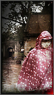 Woman walks through the rain in the Temple of Literature wearing a raincoat and mask, Hanoi, Vietnam, Southeast Asia