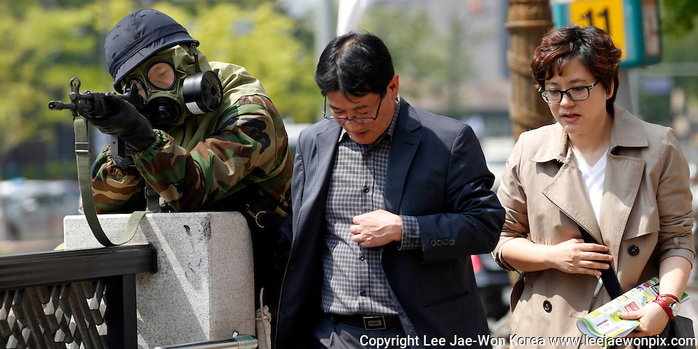 People walk past a South Korean soldier participating in an anti-biochemical terrorism drill in central Seoul May 8, 2013. /Lee Jae-Won