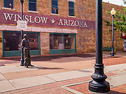 "15 JULY 2012 - WINSLOW, AZ: The Standin' on the Corner park at the intersection of Kinsley Avenue and Second Street in Winslow, AZ. The park is based on the Eagles song, written by Jackson Browne and Glenn Frey, the second verse is ""Well, I'm a standing on a corner, In Winslow, Arizona, And such a fine sight to see. It's a girl, my lord .In a flatbed Ford, Slowin' down to take a look at me"" The park has a statue of Jackson Browne and flatbed Ford parked nearby. There is also a mural of the scene on a wall behind the statue.       PHOTO BY JACK KURTZ"