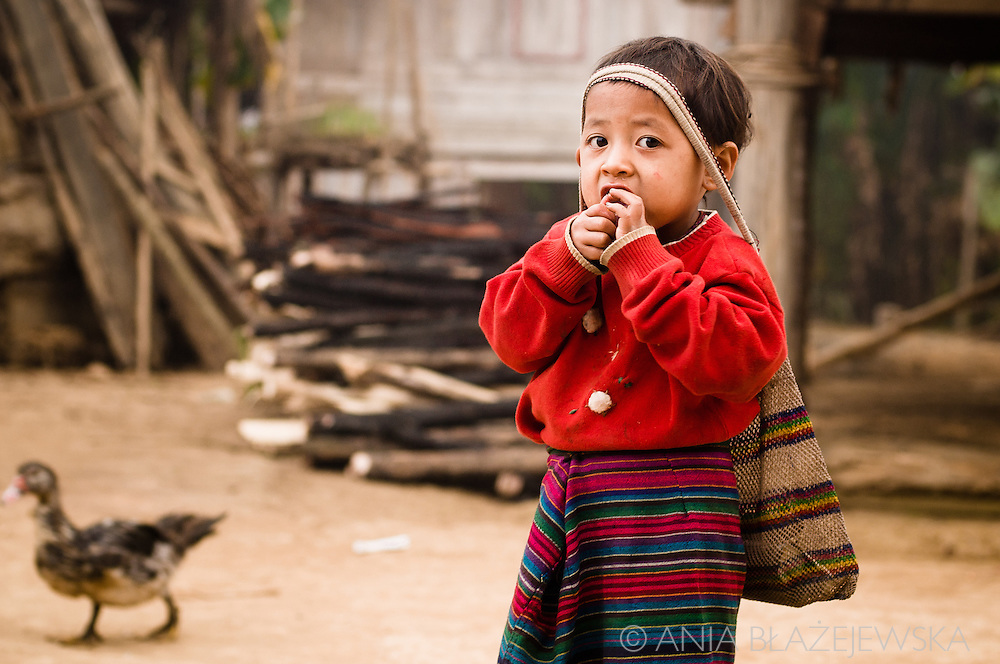 Laos, Ban Nam Pick. A little Khamu girl wearing a red sweater and a bag on her head.