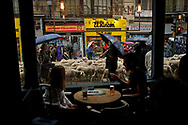 People have drinks at a bar as shepherds lead a flock of sheep along the streets of Madrid city center during the annual livestock migration festival on October 23, 2016 in Madrid, Spain. The transhumance festival has been taking place since 1994 in the Spanish capital to promote the conservation of the ancient paths of livestock transhumance. Livestock transhumance is a millenary tradition for herders to find better weather conditions and natural pasture during winter and summer for their animals. Transhumance also helps to preserve natural landscapes and conserves biodiversity.