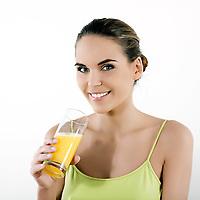 beautiful brunette  woman on white background drinking orange juice