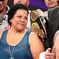 "Dominga Torres-Rivera, mother of fighter Orlando Cruz, smiles at her son during the decision after fighting Jorge Pazos at the Kissimmee Civic Center in Kissimmee, Florida, on Friday, October 19, 2012. The Puerto Rican Cruz recently described himself as ""a proud gay man"" and the first active boxer having pronounced so, in boxing history. Cruz won the fight in a 12-round decision. (AP Photo/Alex Menendez)"