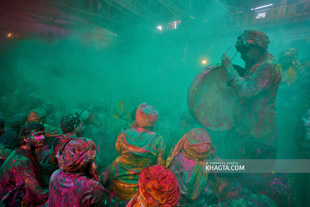 A village drummer removing his glasses while standing in a cloud of green colored powder in Barsana village of Mathura during the celebrations of Braj Holi, the festival of colors.