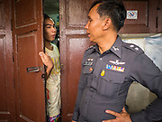 10 SEPTEMBER 2015 - BANGKOK, THAILAND:  A resident on Thetsaban Sai 1 Road, a pedestrian footpath next to Wat Kalayanamit, talks to a police officer while workers demolish Chaiyasit Kittiwanitchapant's home. The man's home, and other homes on the path, will also be demolished in the next week. Authorities started to destroy 54 homes in front of Wat Kalayanamit, a historic Buddhist temple on the Chao Phraya River in the Thonburi section of Bangkok. Government officials, protected by police, seized the house of Chaiyasit Kittiwanitchapant, a Kanlayanamit community leader, who has led protests against the temple's abbot for trying to evict community members whose houses are located around the temple. Work crews went into Chaiyasit's home and took it apart piece by piece. The abbot of the temple said he was evicting the residents, who have lived on the temple grounds for generations, because their homes are unsafe and because he wants to improve the temple grounds. The evictions are a part of a Bangkok trend, especially along the Chao Phraya River and BTS light rail lines, of low income people being evicted from their long time homes to make way for urban renewal.    PHOTO BY JACK KURTZ
